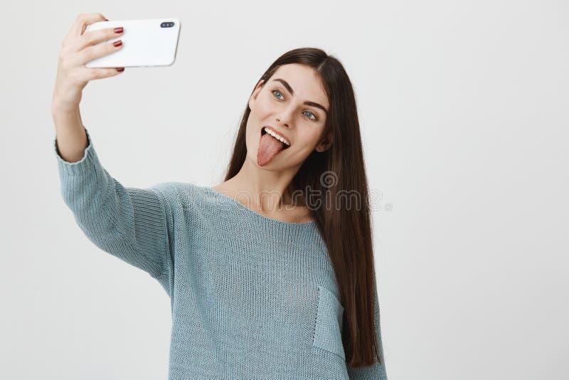 有吸引力和时髦深色的上升的手,当采取在智能手机的selfie,伸出舌头和做逗人喜爱的面孔时 免版税库存图片