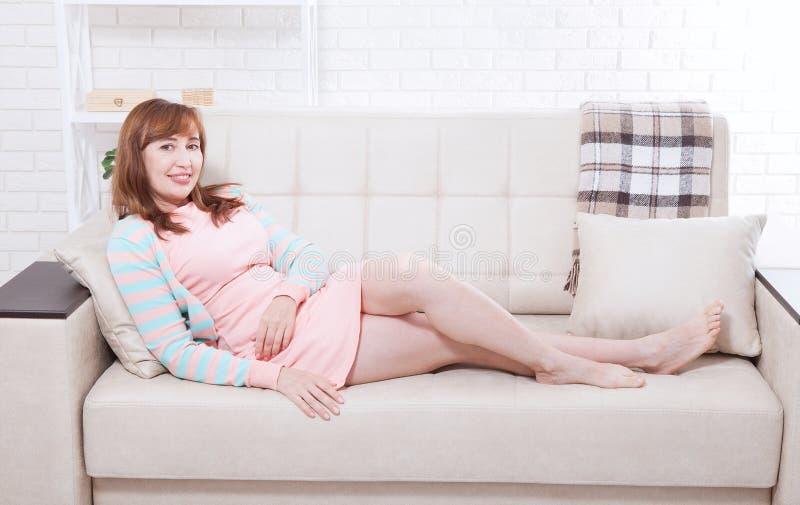 有吸引力和美好的中部变老了在家放松的妇女坐沙发和 更年期 库存图片