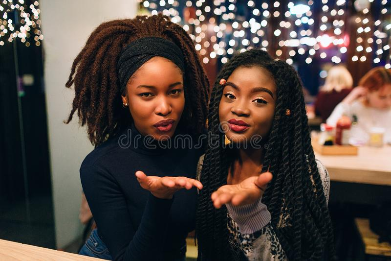 有吸引力和美好的非洲模型看起来平直并且送亲吻 他们一起微笑并且坐 年轻女人看 免版税库存图片