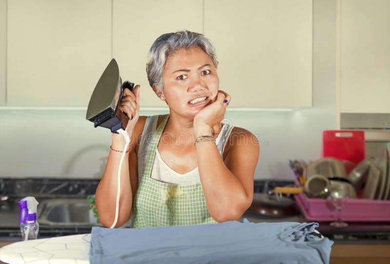 有吸引力和被注重的亚洲中部变老了在家电烙厨房绝望和被淹没的感觉的夫人不快乐在无能为力的面孔 库存照片
