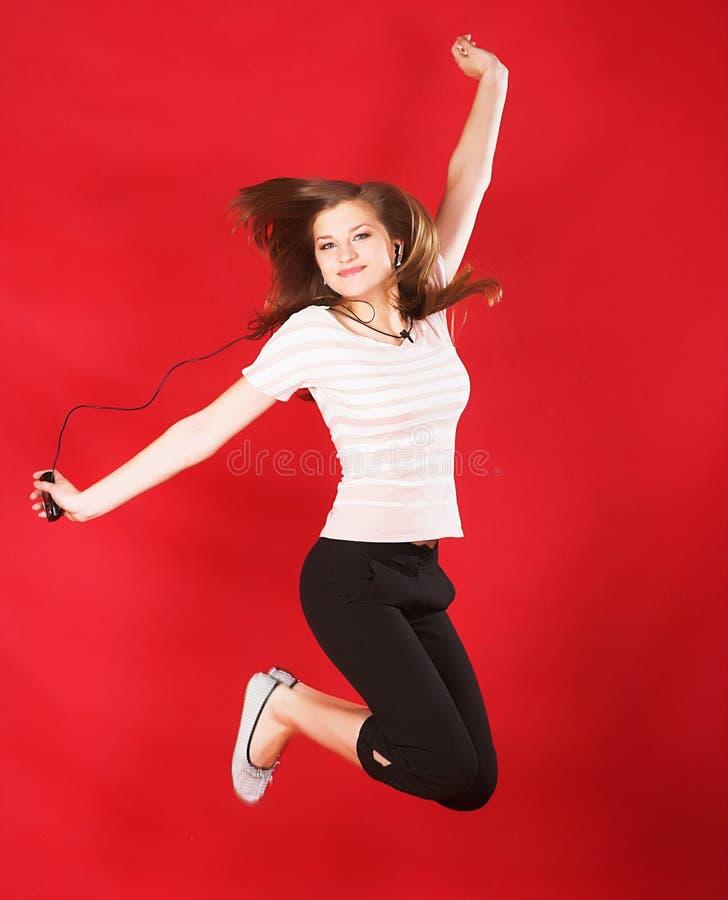 有吸引力女孩跳跃在红色的喜悦 免版税库存照片