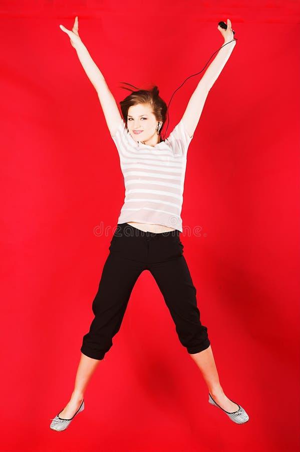 有吸引力女孩跳跃在红色的喜悦 库存照片