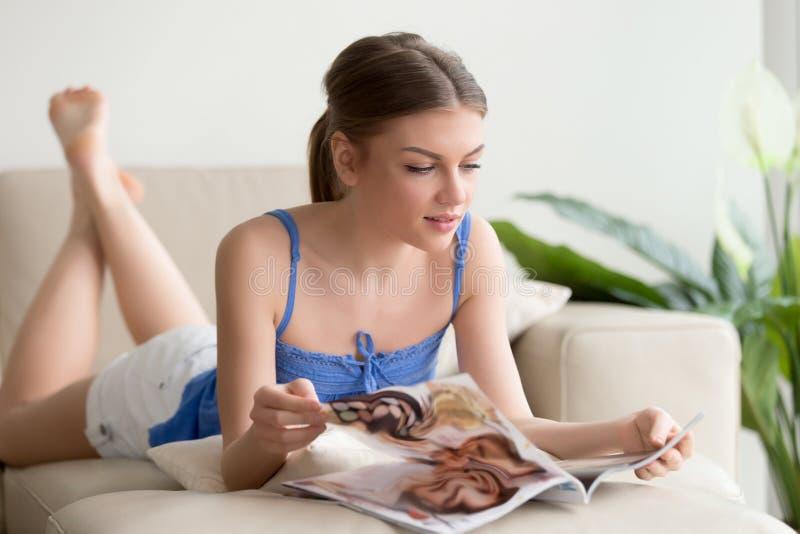有吸引力它女孩在家说谎在长沙发的读书杂志 库存图片