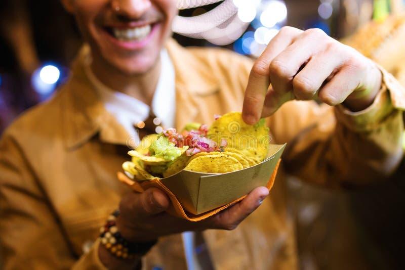有吸引力年轻人参观吃市场和在街道的吃烤干酪辣味玉米片 库存照片