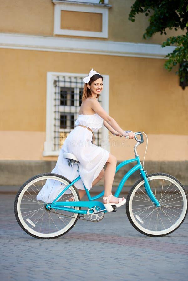 有吸引力年轻女性看对照相机,当骑一辆蓝色葡萄酒自行车时 免版税库存图片