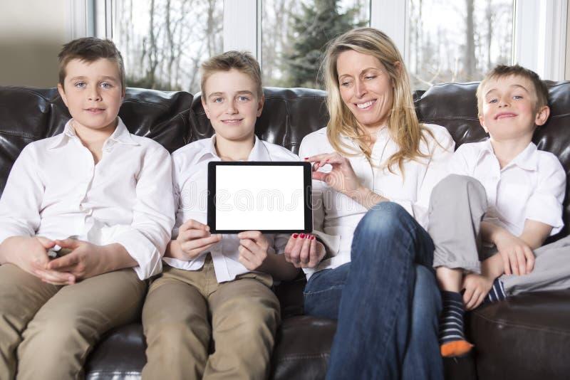 有吸引力愉快,母亲家庭,儿子坐沙发 免版税库存照片