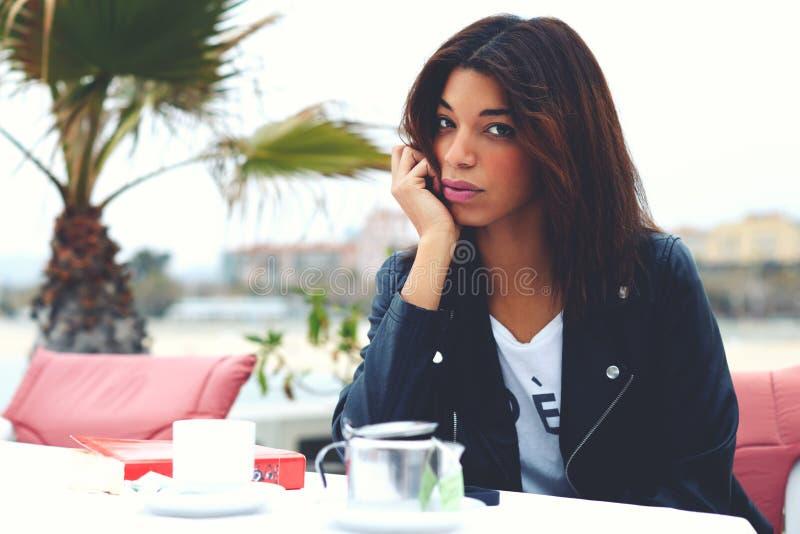 有吸引力时兴女性摆在照相机,当坐在现代边路咖啡馆大阳台时 库存图片