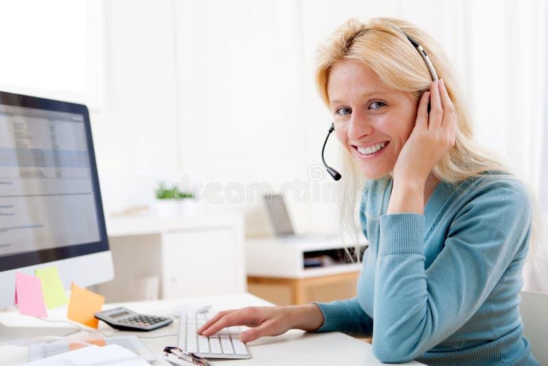 年轻有吸引力白肤金发工作在电话中心 免版税库存图片
