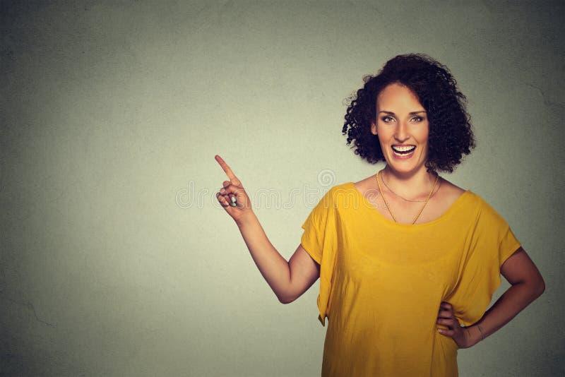 有吸引力的中部变老了指向空白的灰色墙壁背景的妇女 免版税图库摄影