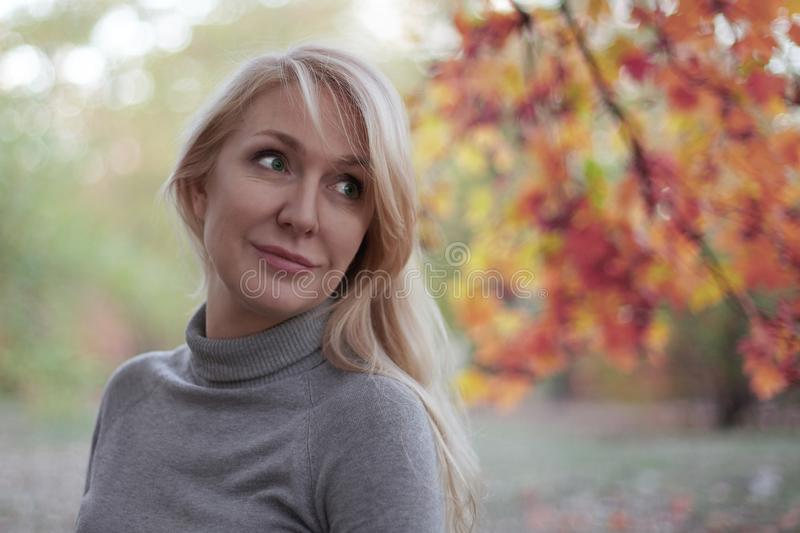 有吸引力的中部在秋天公园变老了有嫉妒的白种人妇女,微笑,单独 便衣 珍贵的年龄概念 免版税库存图片