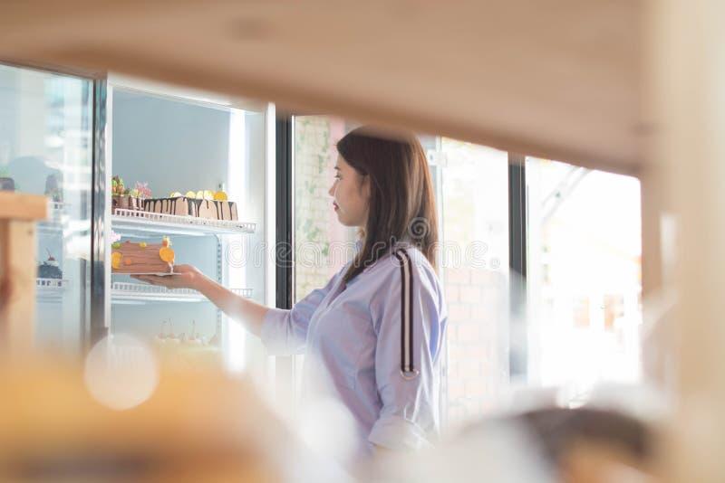有吸引力的亚洲女性开头和从冰箱选择蛋糕在超级市场,寻找生日蛋糕的妇女 免版税图库摄影