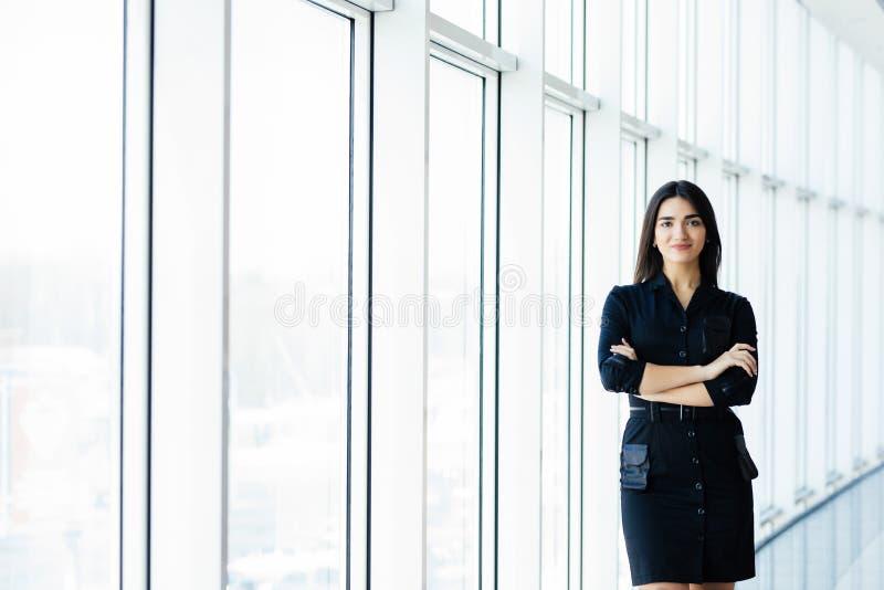 有吸引力的企业微笑的妇女年轻人 愉快的快乐的小姐画象有横渡的胳膊的在商业中心窗口backgro 图库摄影