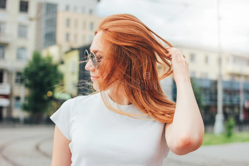 有吸引力的太阳镜的红头发人微笑的女孩接近的画象在街道的便服在城市 免版税库存照片
