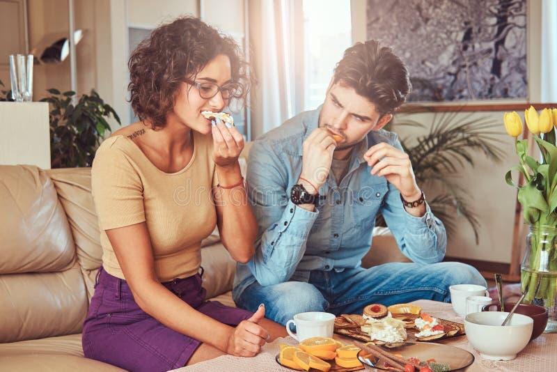有吸引力的夫妇、英俊的有胡子的时髦的人和卷曲在家吃膳食的秀丽女孩 库存照片