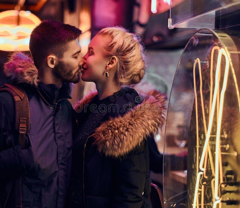 有吸引力的夫妇爱 美女在街道上的夜亲吻她的男朋友身分 免版税库存图片