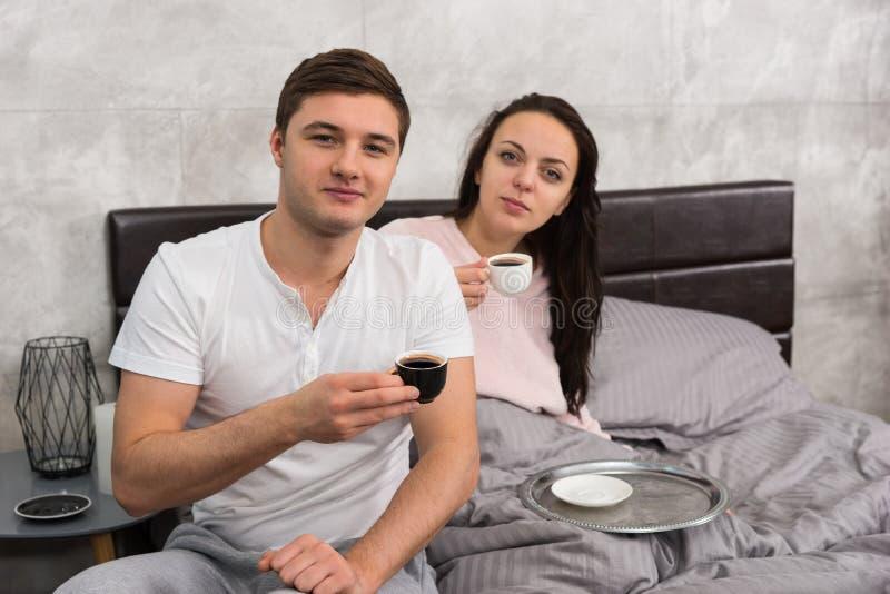 有吸引力的夫妇醒了,拿着一杯咖啡和hav 免版税图库摄影