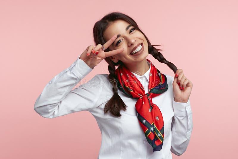 有吸引力的女孩盖子她的与两个手指和平标志的面孔 做在桃红色背景的白色衬衫的秀丽女生面孔 图库摄影