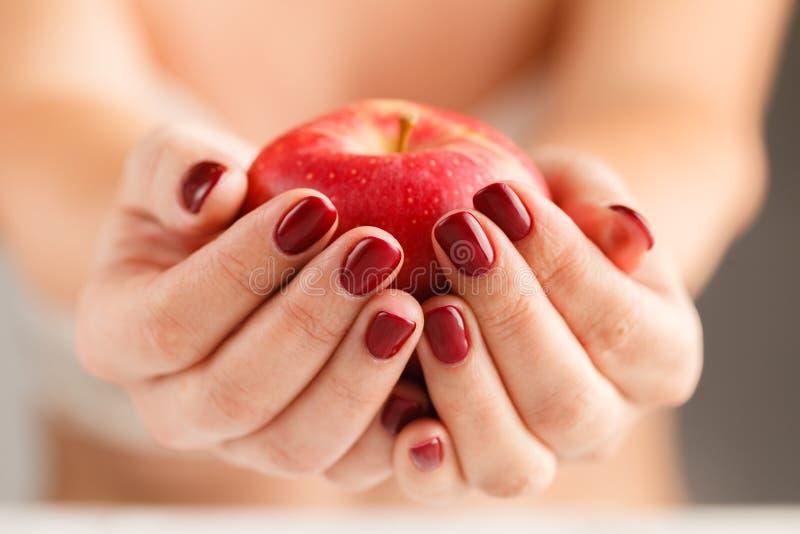 有吸引力的女性举行的果子食物苹果计算机在被修剪的手上 免版税库存照片