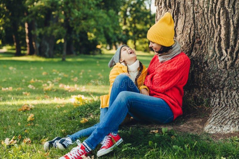 有吸引力的女性模型画象,有与女儿的宜人的交谈,绿草的基于,愉快地看,有喜悦 可爱 免版税库存图片