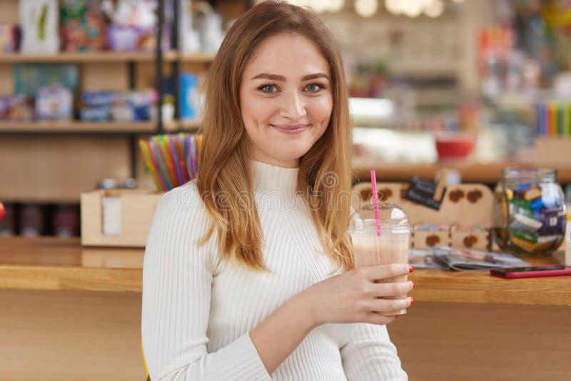 有吸引力的女性饮用的新鲜的鸡尾酒照片,摆在酒吧,穿白色偶然毛线衣,并且牛仔裤,看起来微笑直接地在 免版税库存图片