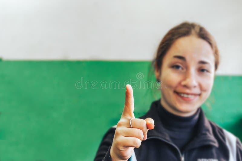 年轻有吸引力的妇女微笑和点手指 免版税图库摄影