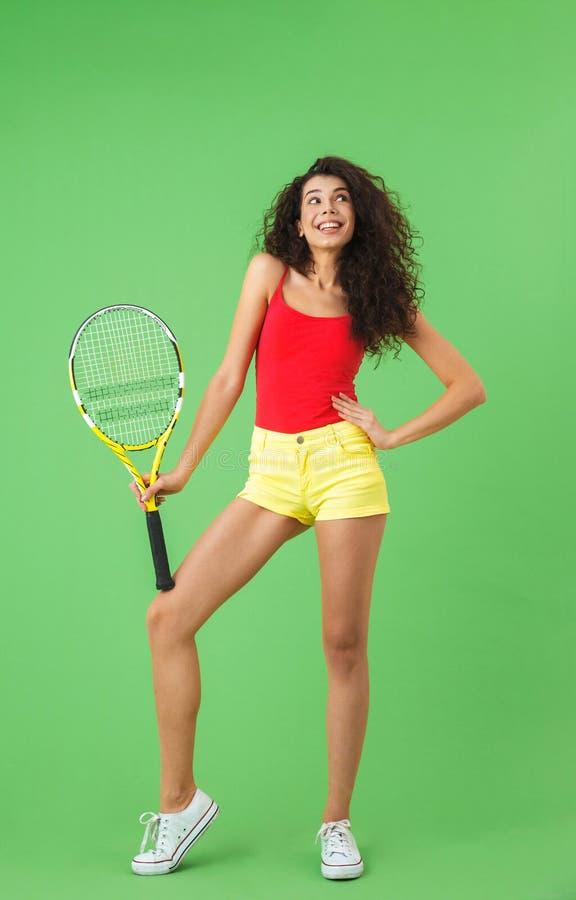 有吸引力的妇女藏品球拍和使用网球画象,当站立对绿色墙壁时 库存照片