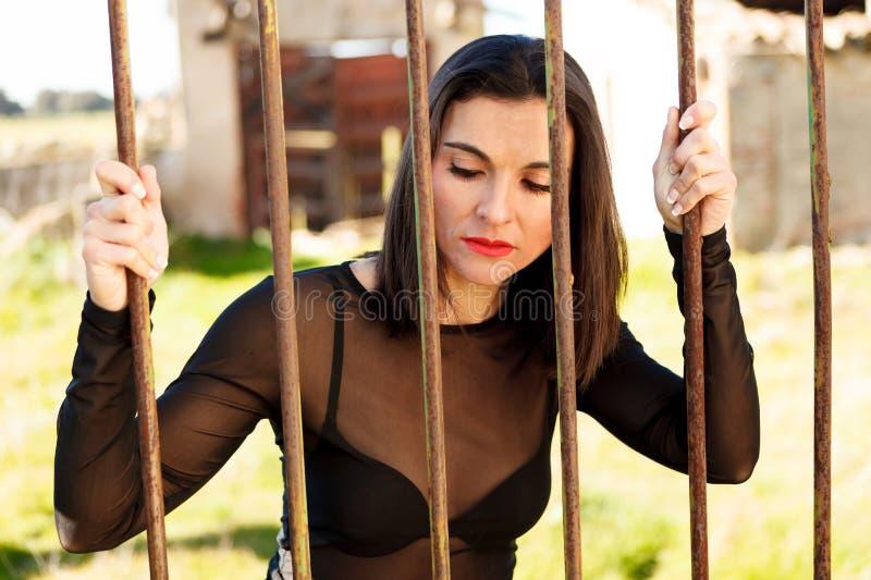 有吸引力的妇女behide酒吧 免版税库存照片