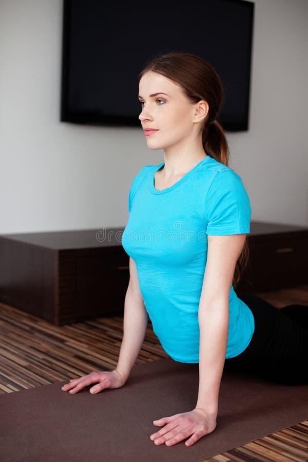 有吸引力的少妇实践的瑜伽在家 图库摄影