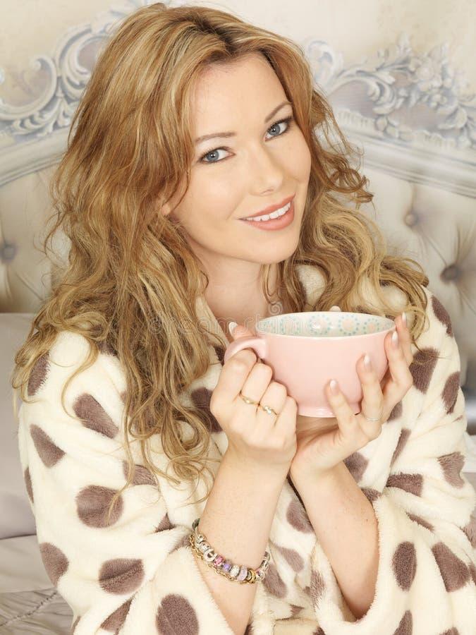 有吸引力的少妇饮用的茶在床上 库存图片
