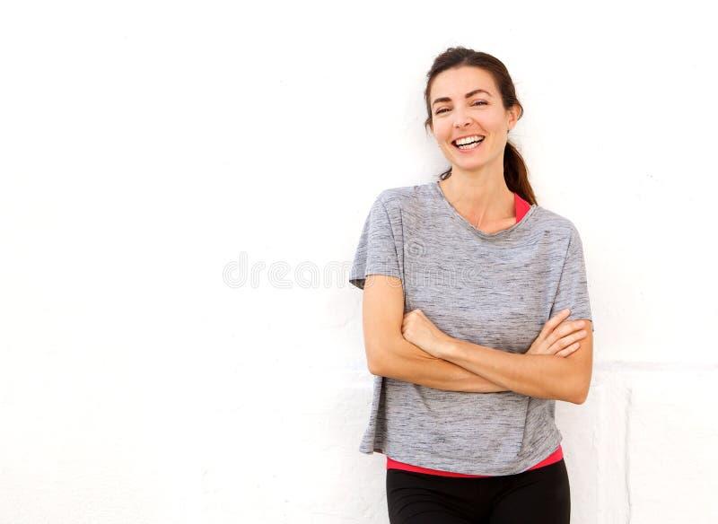 有吸引力的年轻人炫耀微笑与胳膊的妇女横渡对白色墙壁 库存照片