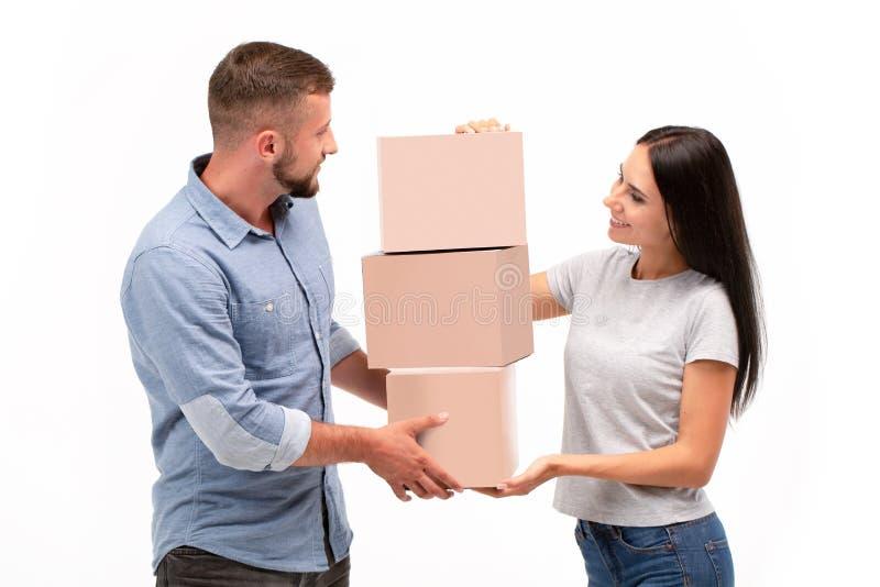 有吸引力的年轻在白色背景的夫妇运载的移动的箱子 免版税库存照片
