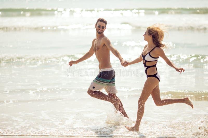 有吸引力的年轻夫妇获得在海滩的乐趣 库存图片