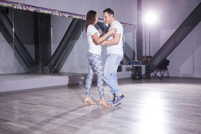 有吸引力的年轻夫妇跳舞在大大厅里 体育和激情 库存照片