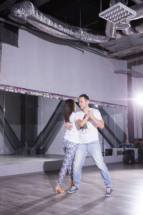 有吸引力的年轻夫妇跳舞在大大厅里 体育和激情 免版税图库摄影
