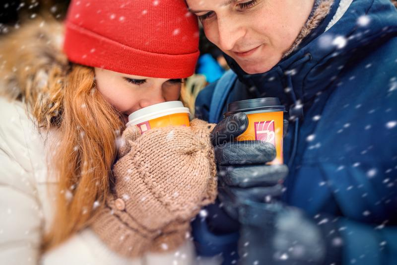 有吸引力的年轻夫妇饮用的咖啡和茶的特写镜头水平的画象在蓬松降雪期间 库存照片