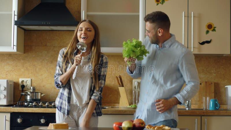 有吸引力的年轻快乐的夫妇有乐趣跳舞和唱歌,当在家时烹调在厨房 图库摄影
