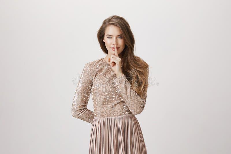有吸引力的年轻欧洲模型画象在掩藏事的晚礼服的后边后面,微笑,当显示嘘时 免版税库存图片
