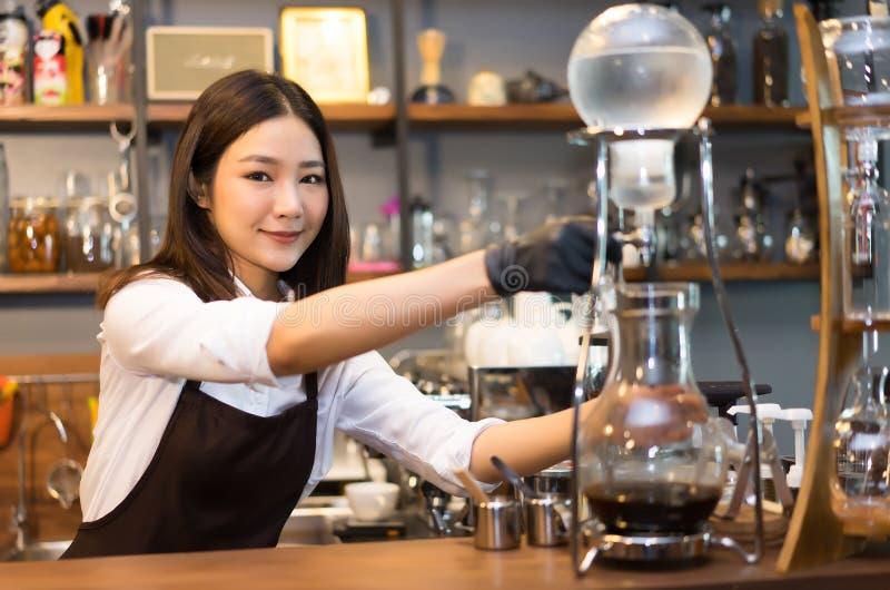 有吸引力的年轻美丽的白种人barista做被冰的缓慢的滴水 免版税库存照片