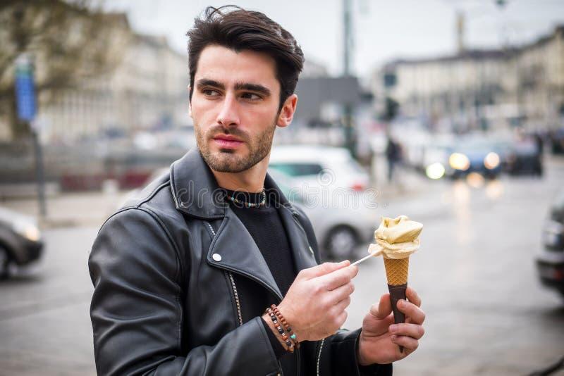有吸引力的年轻食人的冰淇淋户外在城市 免版税库存图片