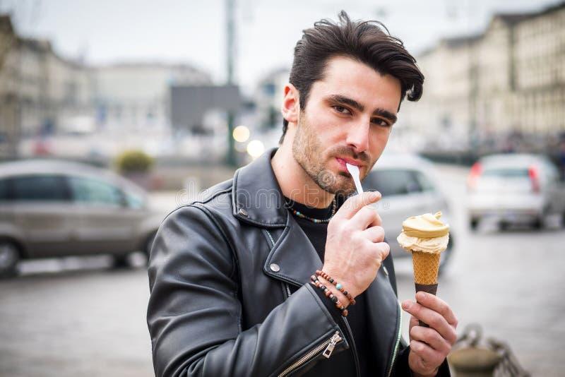 有吸引力的年轻食人的冰淇淋户外在城市 免版税库存照片