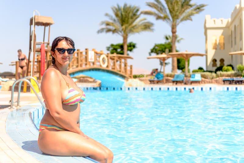 有吸引力的微笑的肥满妇女坐的游泳池边 库存照片