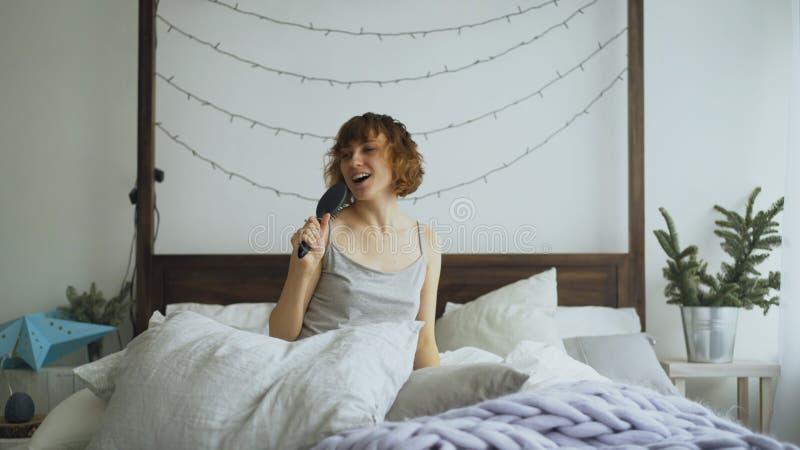有吸引力的快乐的妇女跳舞和唱歌与梳子喜欢在家坐在床上的话筒 免版税库存图片