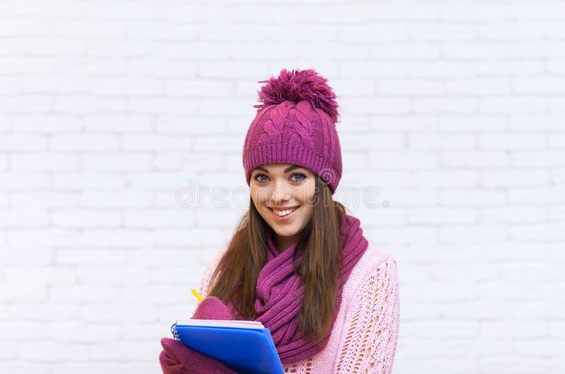 有吸引力的拿着文件夹铅笔的桃红色帽子的学生微笑十几岁的女孩 库存照片