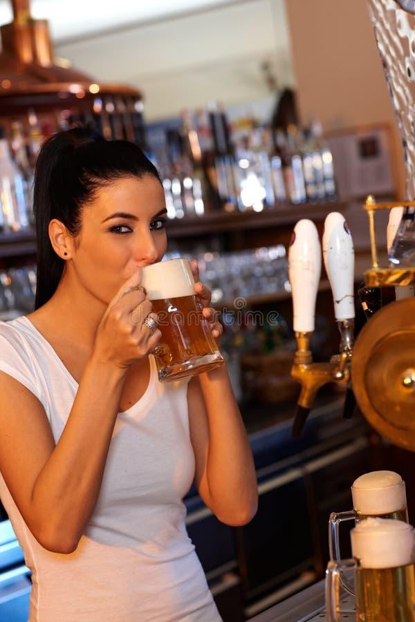 有吸引力的新鲜酒吧招待品尝桶装啤酒 免版税图库摄影