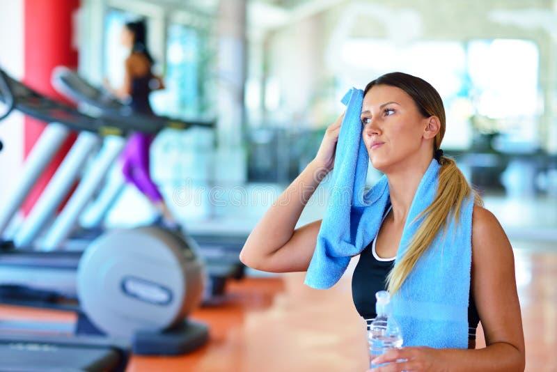 有吸引力的照相机特写镜头健身增强的微笑衡量妇女 健身房饮用水的美丽的女孩,与蓝色毛巾 免版税图库摄影