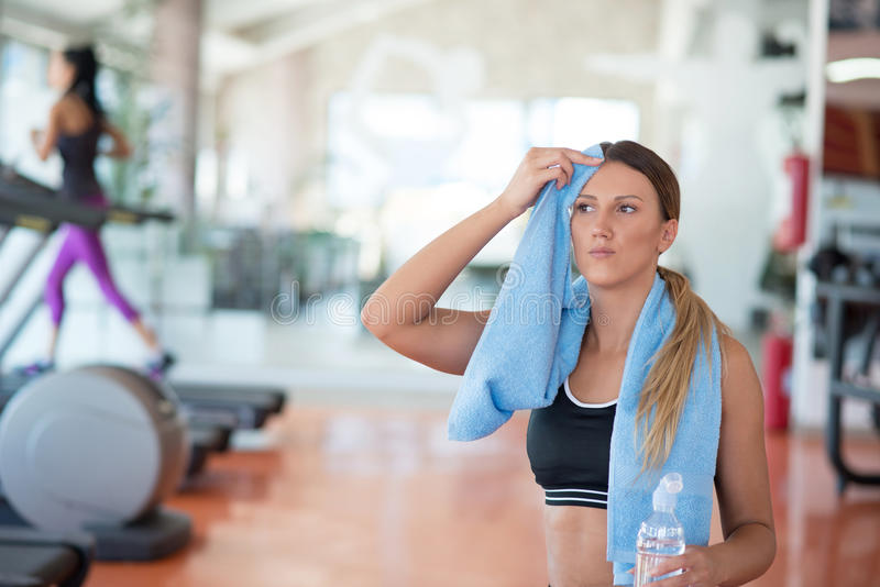 有吸引力的照相机特写镜头健身增强的微笑衡量妇女 健身房饮用水的美丽的女孩,与蓝色毛巾 库存照片