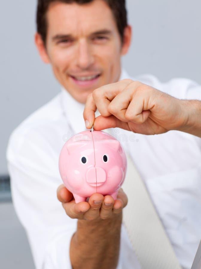 有吸引力的生意人货币piggybank节省额 图库摄影