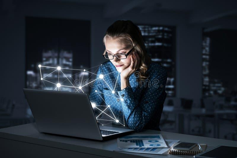 有吸引力的白肤金发的佩带的玻璃在使用膝上型计算机的黑暗的办公室 M 免版税库存照片