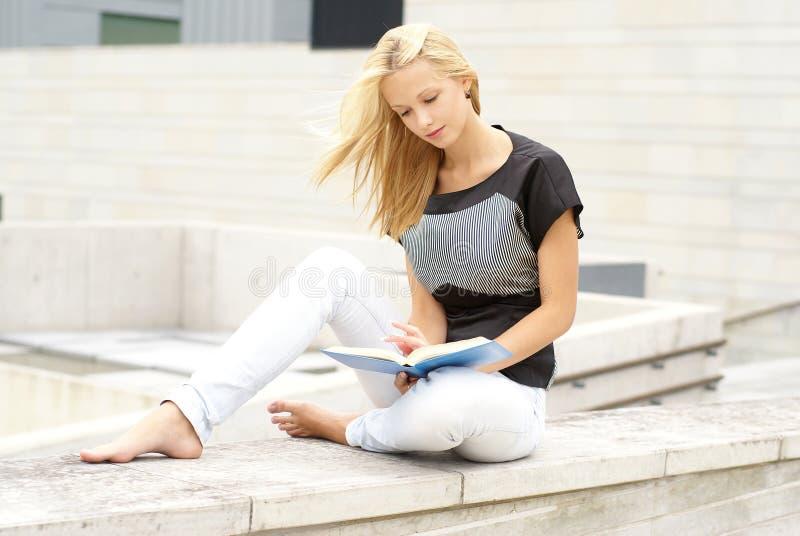 有吸引力的白肤金发的女孩读取年轻&# 免版税库存照片