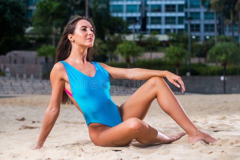有吸引力的苗条游泳衣式样摆在与度假旅馆的沙子在背景中 免版税图库摄影
